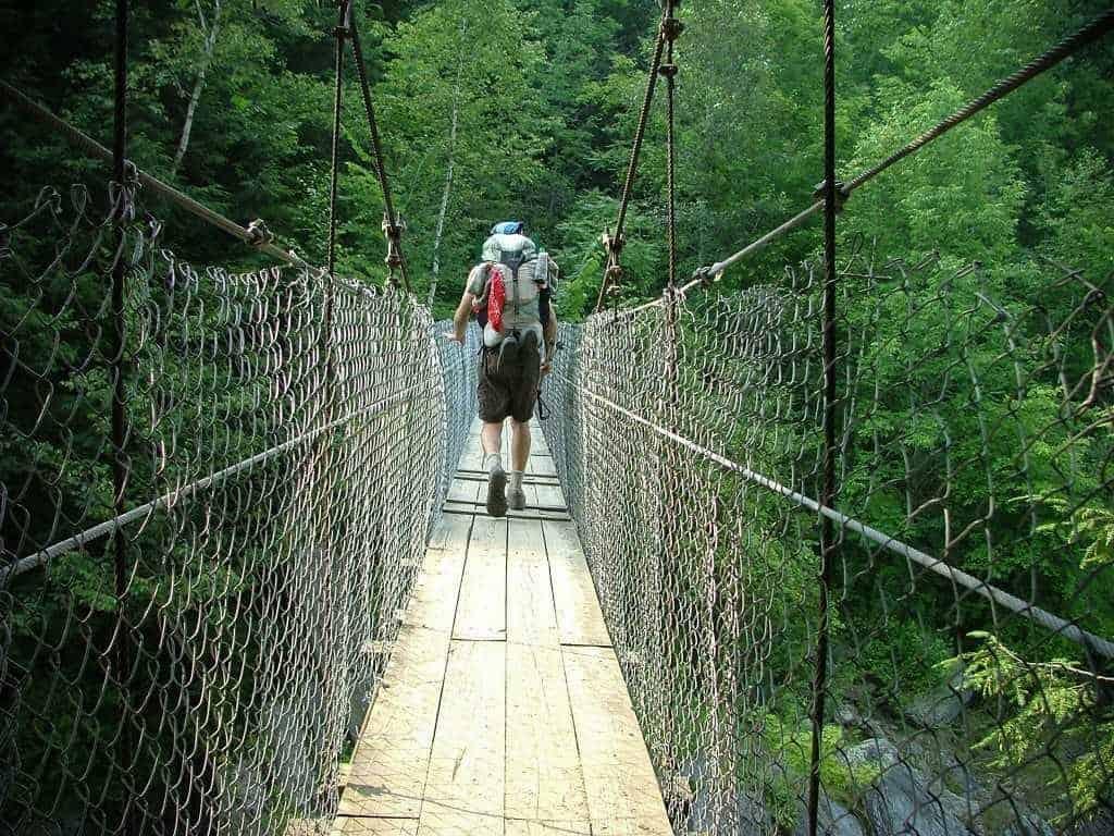 hike the Appalachian trail: Hiker crossing a bridge
