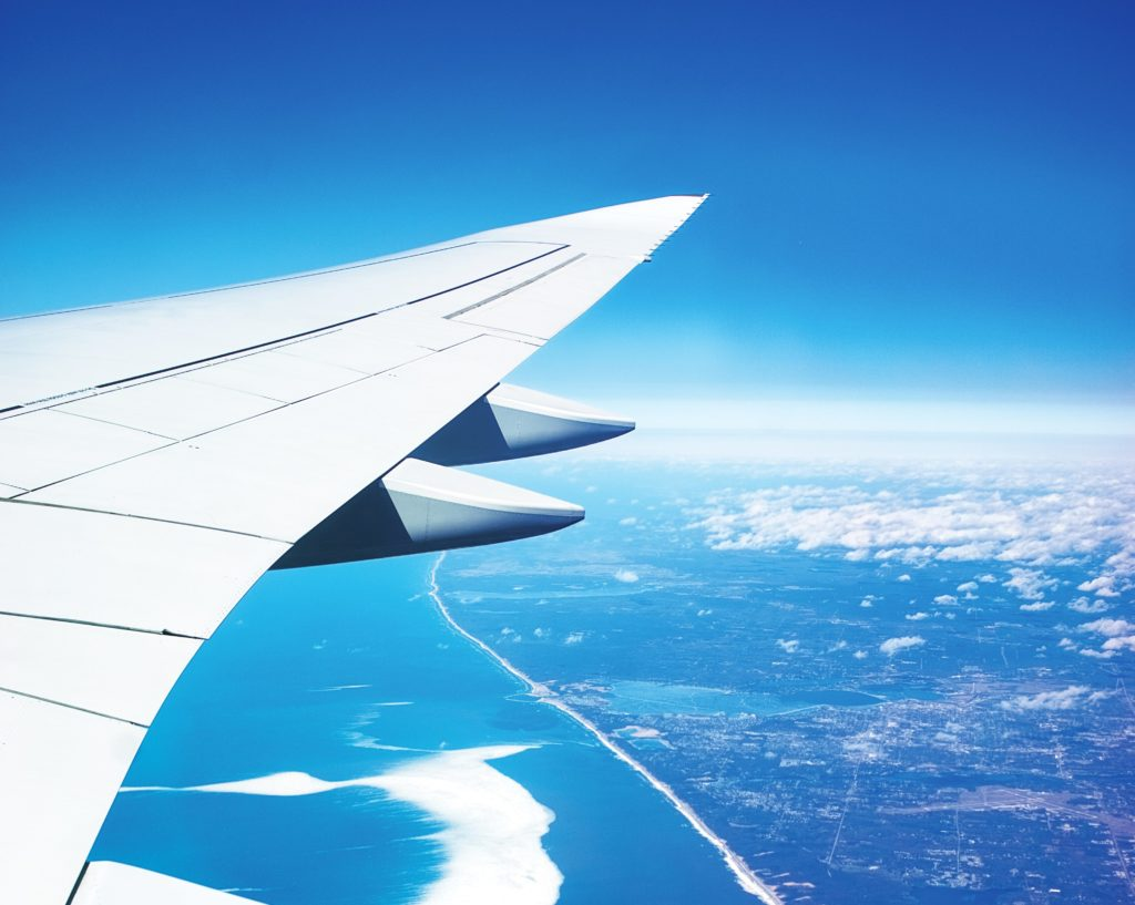 airplane wing over a coast line and ocean